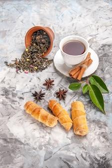 白いテーブルのティーケーキペストリーにベーグルとお茶のトップビューカップ