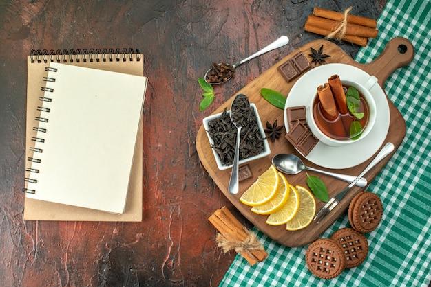 어두운 배경 꽃색 쿠키 차 커피 맛에 비스킷과 레몬을 넣은 차 한 잔