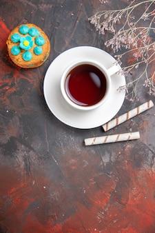 暗いテーブルの色の暗い式典のお茶にビスケットとお茶のトップビューカップ