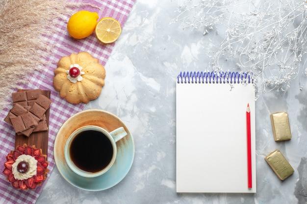 Вид сверху чашка чая с тортом, лимонным блокнотом и плитками шоколада на белом столе, торт, сладкий сахарный шоколад