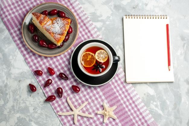 白い表面にケーキスライスとお茶のトップビューカップビスケットケーキ甘いパイ