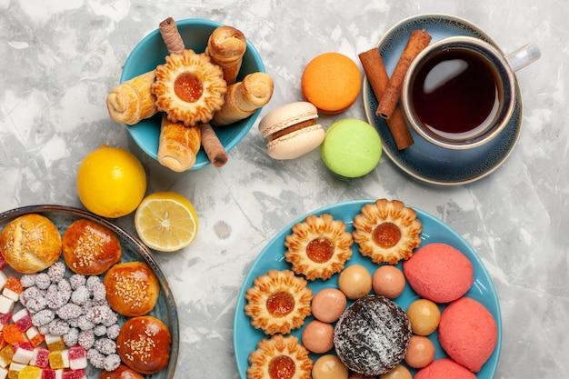 흰색 표면에 케이크 쿠키와 마카롱 차의 상위 뷰 컵