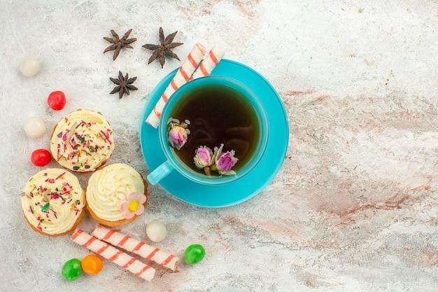 白い表面のお茶のデザートビスケットケーキパイにキャンディーとケーキとお茶のトップビューカップ