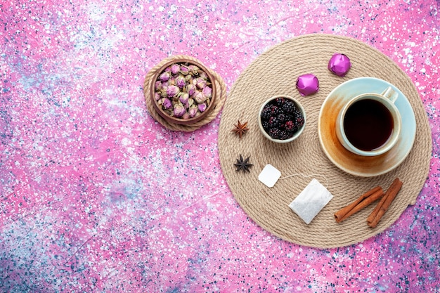 분홍색 배경에 사탕과 계 피와 차의 상위 뷰 컵.