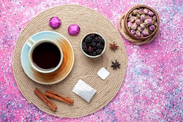 ピンクの背景にキャンディーとシナモンとお茶のトップビューカップ。
