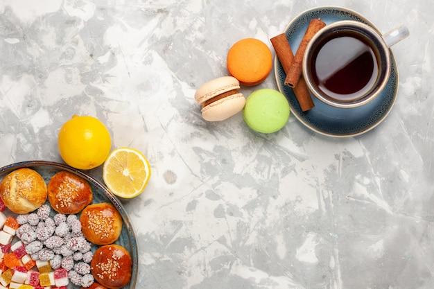 흰색 표면에 사탕과 작은 케이크 마카롱과 차의 상위 뷰 컵