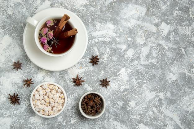 白い背景の上のキャンディーとお茶のトップビューカップは、熱い甘い砂糖の朝食を飲みます