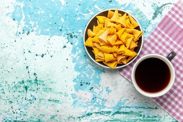 Вид сверху чашка чая с чипсами на голубой поверхности