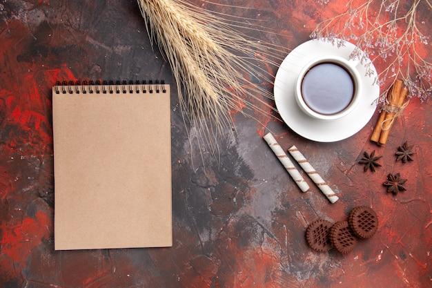 ダークデスクティークッキービスケットにチョコクッキーとお茶のトップビューカップ
