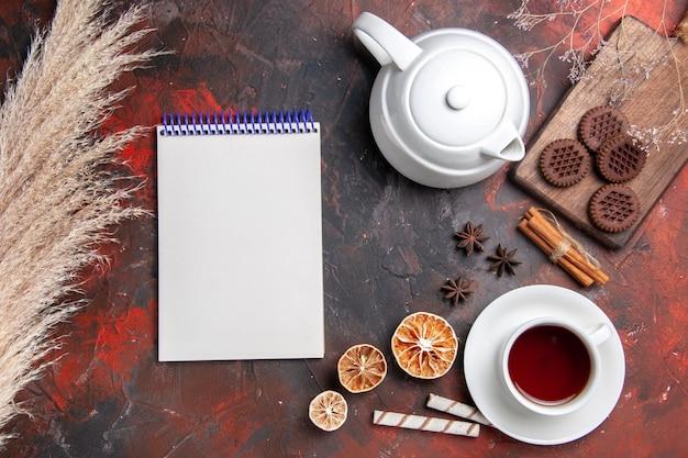 Вид сверху чашка чая с шоколадным печеньем на темном полу фото чайное печенье