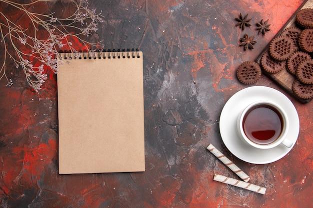 Вид сверху чашка чая с шоколадным печеньем на темном столе, печенье с чаем
