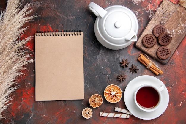 暗いテーブルの上のチョコクッキーとお茶のトップビューカップ写真ティービスケット