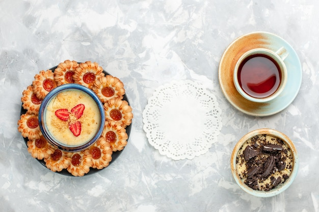 밝은 흰색 책상 쿠키 초콜릿 케이크 베이킹 파이 설탕에 초콜릿 쿠키 디저트와 잼 쿠키와 차의 상위 뷰 컵