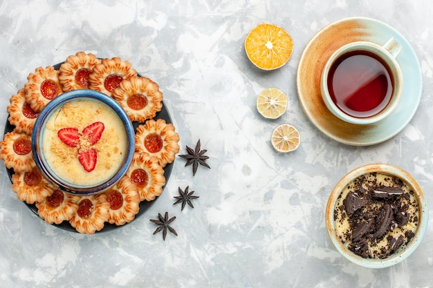 ライトホワイトのデスククッキーチョコレートケーキ焼きパイシュガースウィートにチョコレートクッキーデザートとジャムクッキーとお茶のトップビューカップ