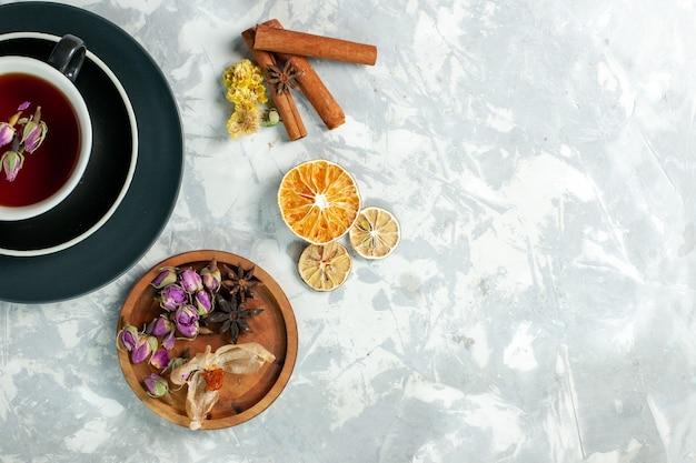 ライトホワイトの表面のお茶の甘い飲み物の花にシナモンと花とお茶のトップビューカップ