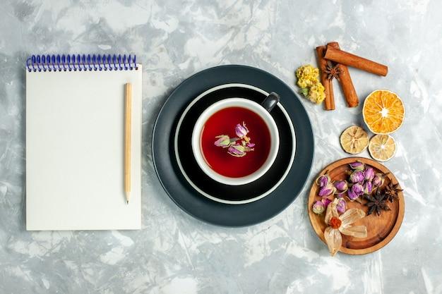 흰 벽 차 달콤한 음료 꽃에 계 피와 메모장 차의 상위 뷰 컵