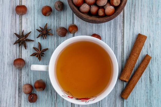 Вид сверху чашка чая с корицей и орехами на сером фоне