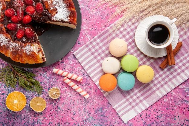 ピンクのデスクケーキビスケットクッキー甘い砂糖にシナモンケーキとフレンチマカロンとお茶のトップビューカップ