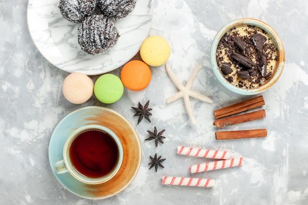 Вид сверху чашка чая с макаронами с корицей и шоколадными тортами на белом столе, выпечка торта, бисквитного сахара, сладкого пирога