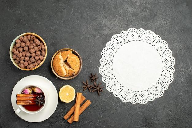 濃い灰色の表面のお茶の飲み物の儀式の甘いシナモンとお茶のトップビューカップ