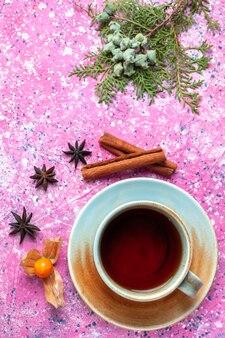 Чашка чая с корицей на розовом столе вид сверху.