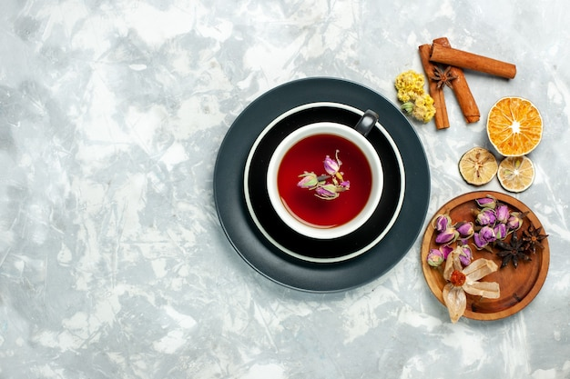白い壁のお茶の甘い飲み物の花にシナモンとお茶のトップビューカップ