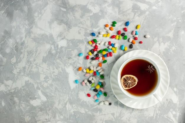 明るい白い机の上にカラフルなさまざまなキャンディーとお茶のトップビューカップ
