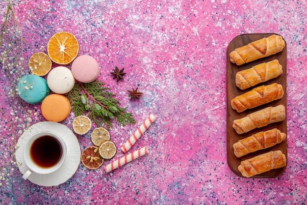 ピンクのデスクケーキビスケットシュガースイートパイティークッキーにカラフルなフレンチマカロンとベーグルとお茶のトップビューカップ