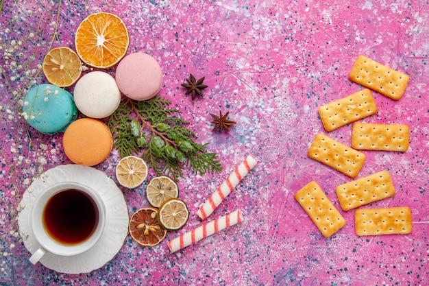 ピンクの壁のケーキビスケットシュガー甘いパイティークッキーにカラフルなフレンチマカロンとクラッカーとお茶のトップビューカップ