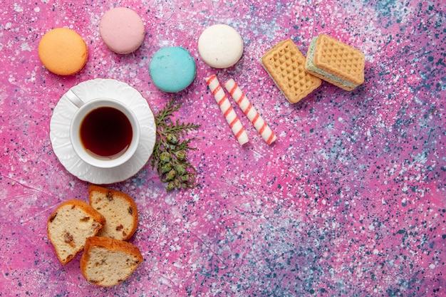 ピンクの壁のケーキにカラフルなフレンチマカロンとワッフルを添えたトップビューのお茶ビスケットシュガースイートパイティー