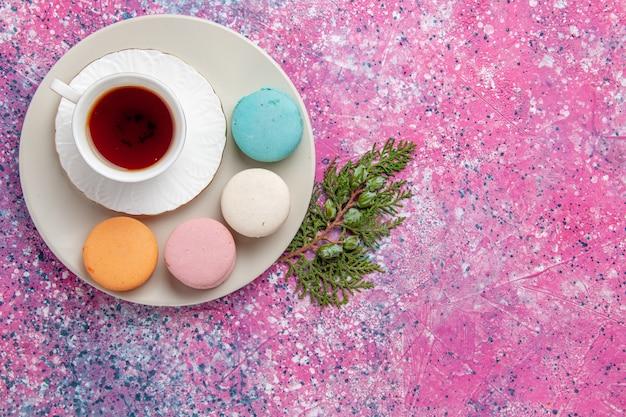 ピンクの表面にカラフルなフレンチマカロンとお茶のトップビューカップ