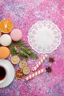 분홍색 표면에 화려한 프랑스 마카롱과 차의 상위 뷰 컵