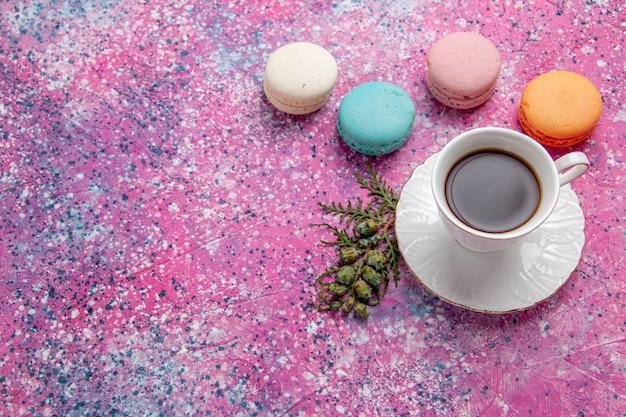 ピンクの壁のケーキビスケットシュガー甘いパイにカラフルなフレンチマカロンとお茶のトップビューカップ