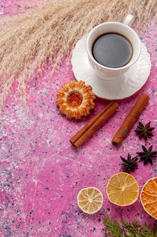 ピンクの背景色のお茶の甘いビスケットにクッキーとシナモンとお茶のトップビューカップ