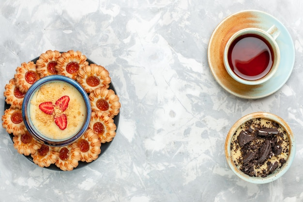 ライトホワイトのデスクにクッキーデザートとジャムクッキーを添えたトップビューのお茶クッキーチョコレートケーキ焼きパイシュガースウィート