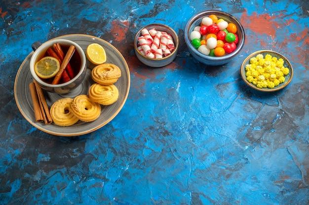 青いテーブルビスケットキャンディーティーにクッキーとキャンディーとお茶のトップビューカップ