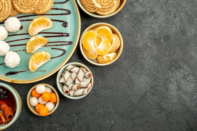 灰色のテーブルのクッキーケーキビスケットにクッキーとキャンディーとお茶のトップビューカップ