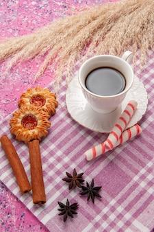 밝은 분홍색 책상 비스킷 설탕 쿠키 달콤한 쿠키와 계피와 차의 상위 뷰 컵