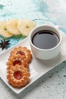 Вид сверху чашка чая с печеньем и сушеными кольцами ананаса на голубой поверхности
