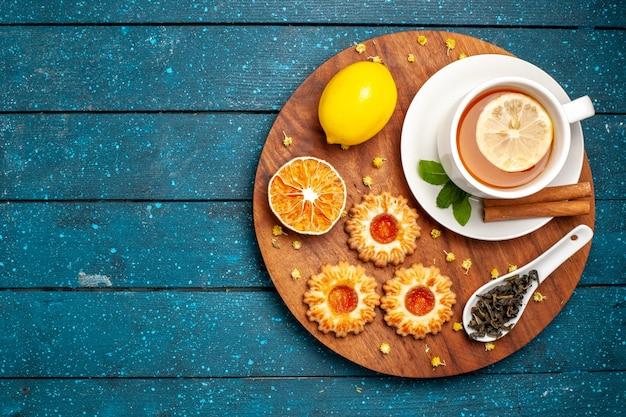 Вид сверху чашка чая с печеньем и лимоном на синем столе