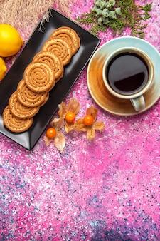 Вид сверху чашка чая с печеньем и лимоном на светло-розовом столе.