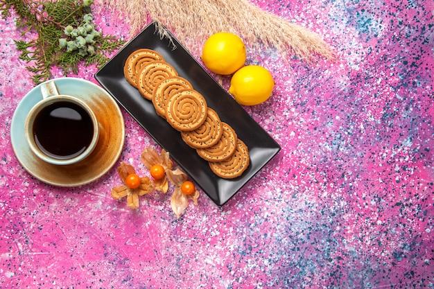 Вид сверху чашка чая с печеньем и лимоном на розовом столе.