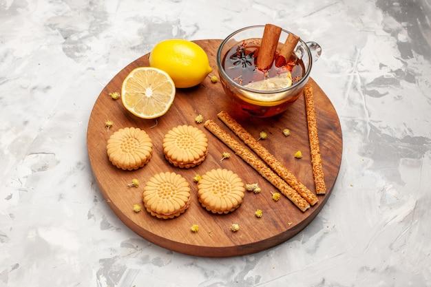 空白の上のクッキーとレモンとお茶のトップビューカップ