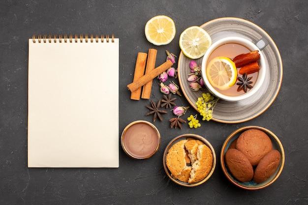 暗い表面のお茶砂糖フルーツビスケット甘いクッキーにクッキーとレモンスライスとお茶のトップビューカップ