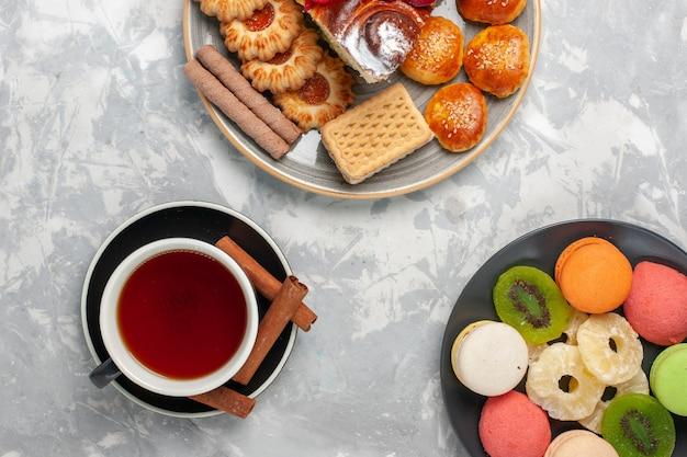 白い表面にクッキーと小さなケーキとお茶のトップビューカップ