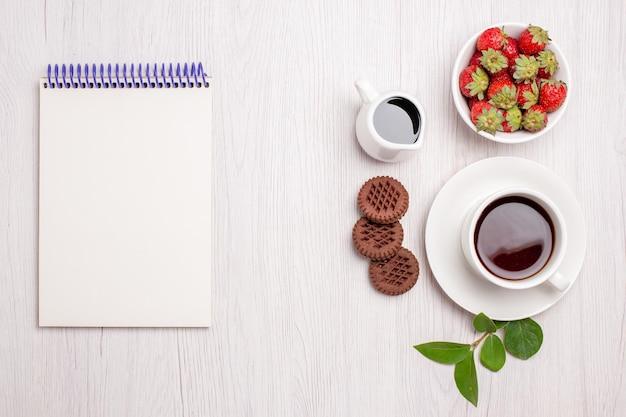 白い机の砂糖茶クッキー甘いビスケットの上にクッキーとイチゴのお茶のトップ ビュー