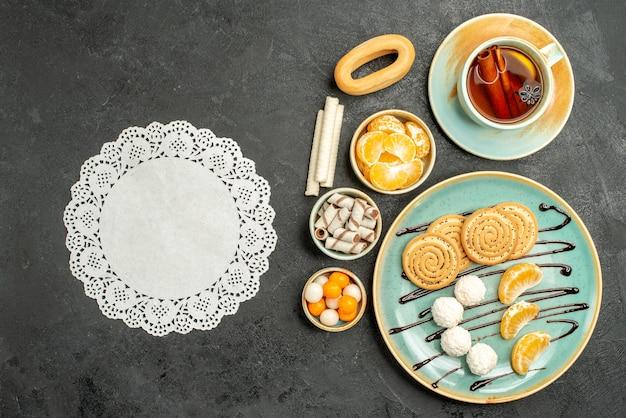Вид сверху чашка чая с печеньем и мандаринами на темном фоне
