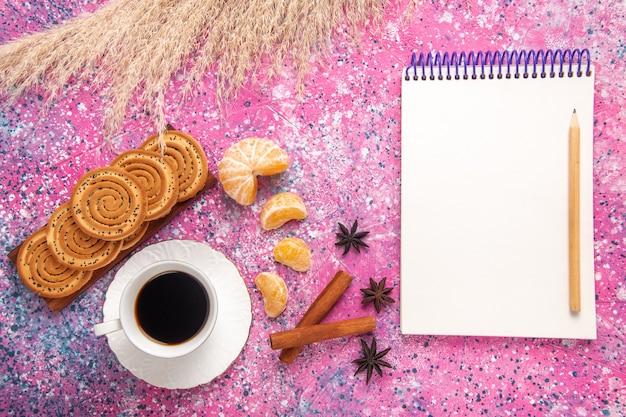 淡いピンクの机の上にクッキーシナモンとみかんとお茶のトップビューカップ。