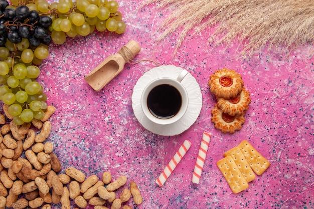 ピンクの机の上のクッキークラッカーピーナッツと新鮮なブドウとお茶のトップビューカップビスケットフルーツナッツの色クリスプ