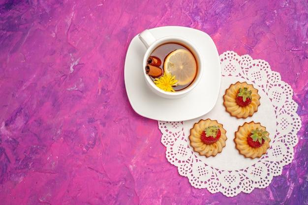 ピンクのテーブルキャンディーカラーティービスケットにクッキーとお茶のトップビューカップ